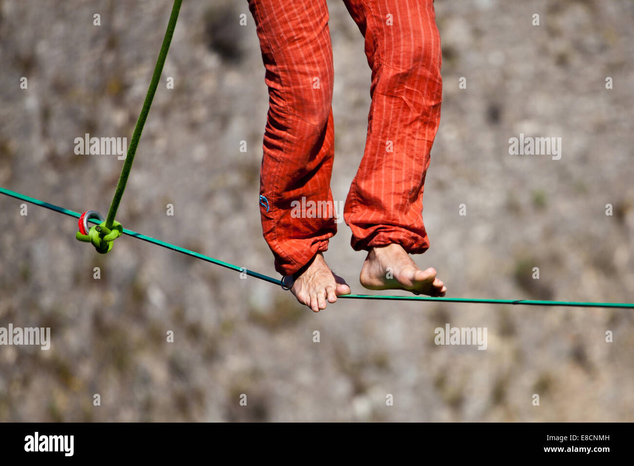 Slacklining is a practice in balance that typically uses nylon or polyester webbing tension between two anchor points. Stock Photo