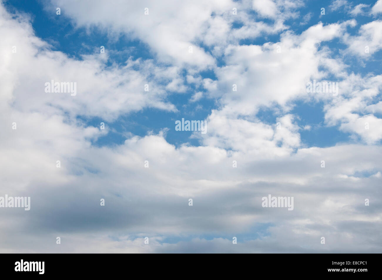 Blue sky with intermittent cloud cover - Stock Image