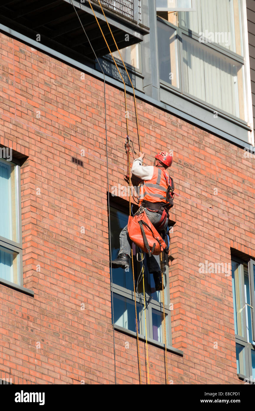 Workman using rope access technique at an apartment block, Whitworth Street, Manchester, England, UK Stock Photo