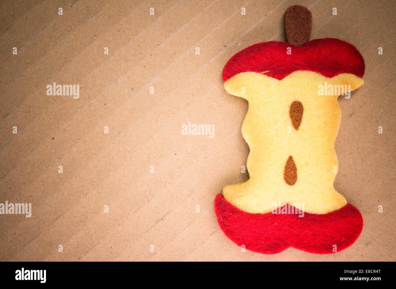 felt apple core on a cardboard surface - Stock Image