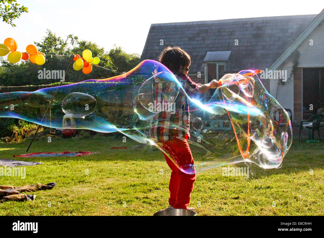 A young child making bubbles in a garden on a summers day During a garden party. - Stock Image