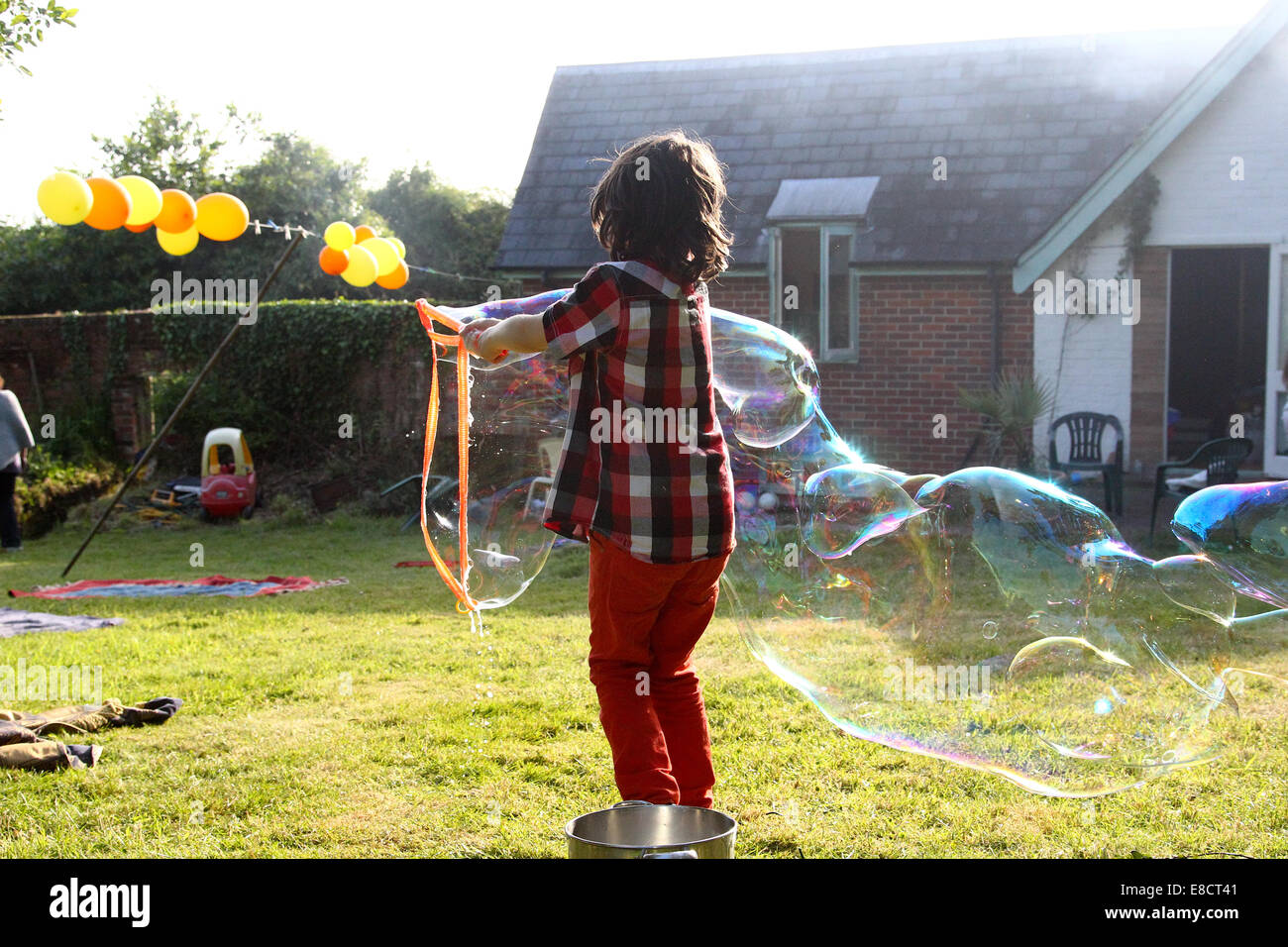 A young child making bubbles in a garden on a summers day During a garden party. Stock Photo