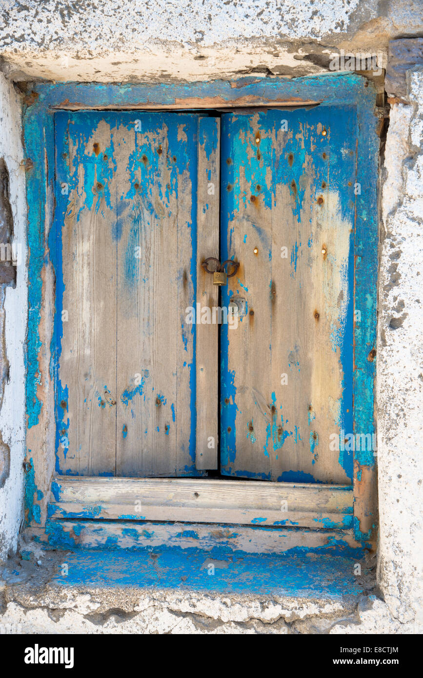 old colourless blue wooden shutter in greece - Stock Image
