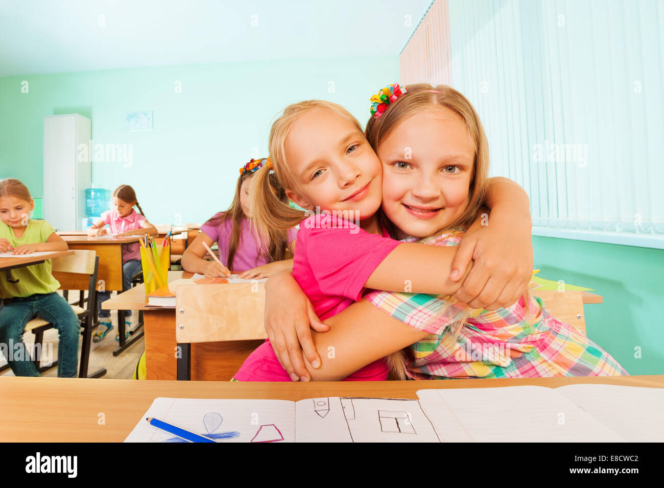 Happy girls in a cuddle sitting together at desk - Stock Image