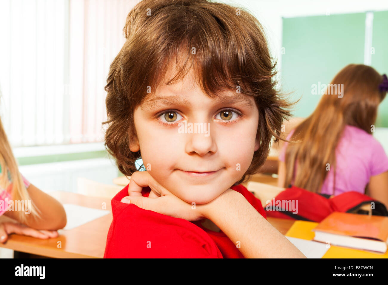 Portrait of cute boy looking straight in classroom - Stock Image