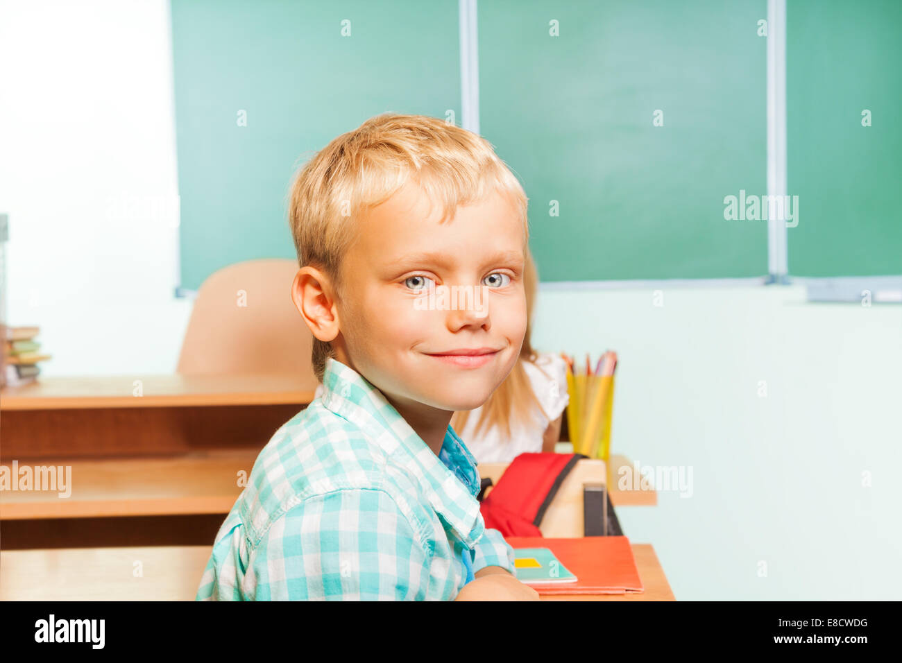 Smiling boy sits at desk with blackboard behind - Stock Image