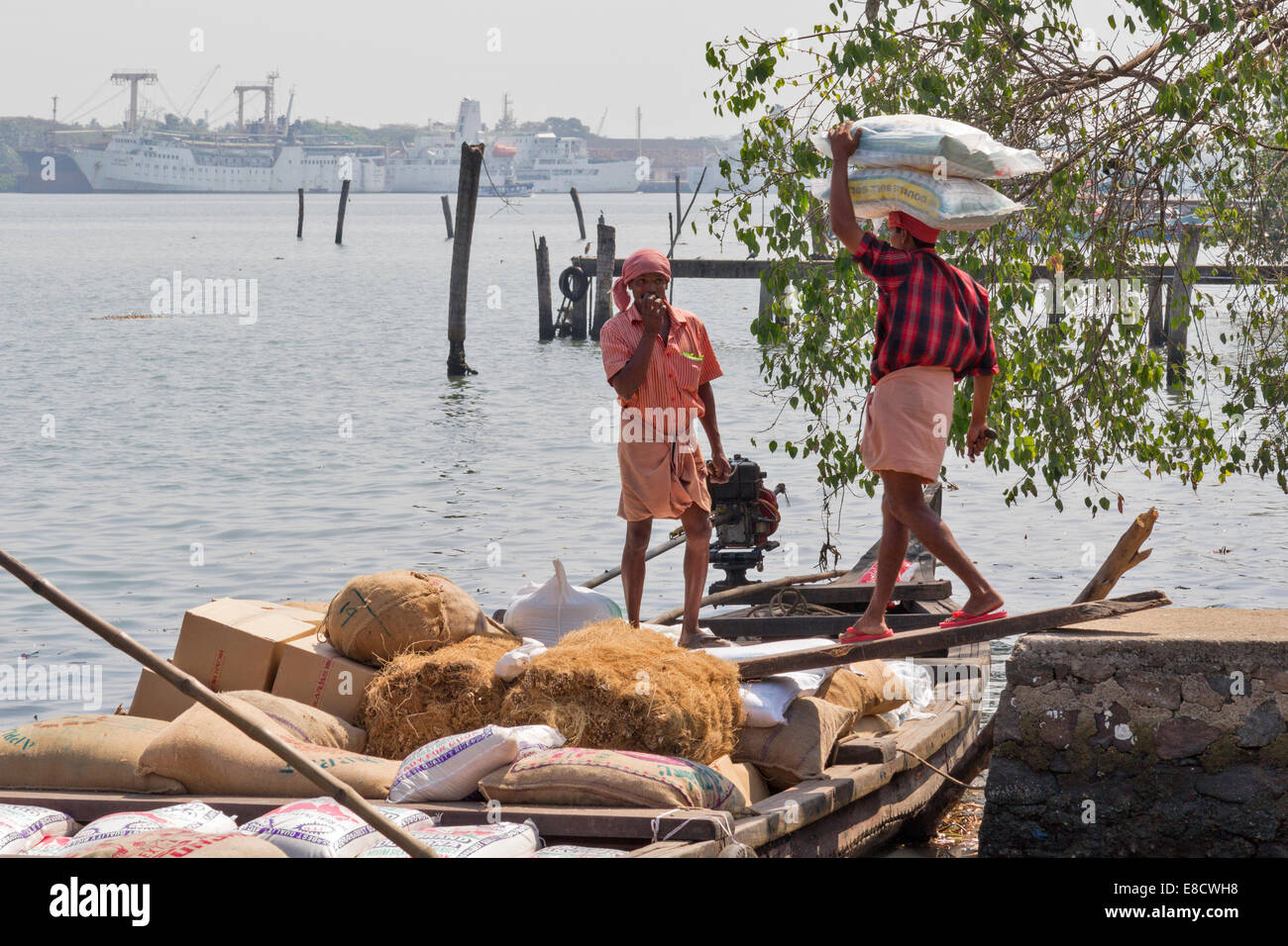 TWO MEN LOADING AN OLD WOODEN BOAT WITH HEAVY SACKS OF FOOD IN PORT KOCHI OR COCHIN INDIA - Stock Image