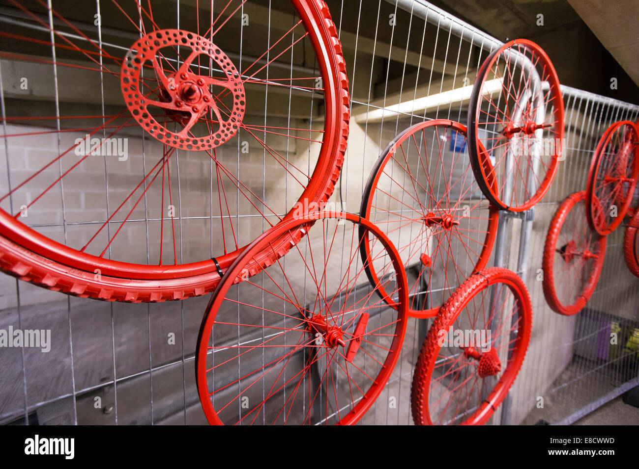 Red bicycle wheels on display at Parkour Ride a multi-discipline cycling event held in an abandoned multi-storey - Stock Image