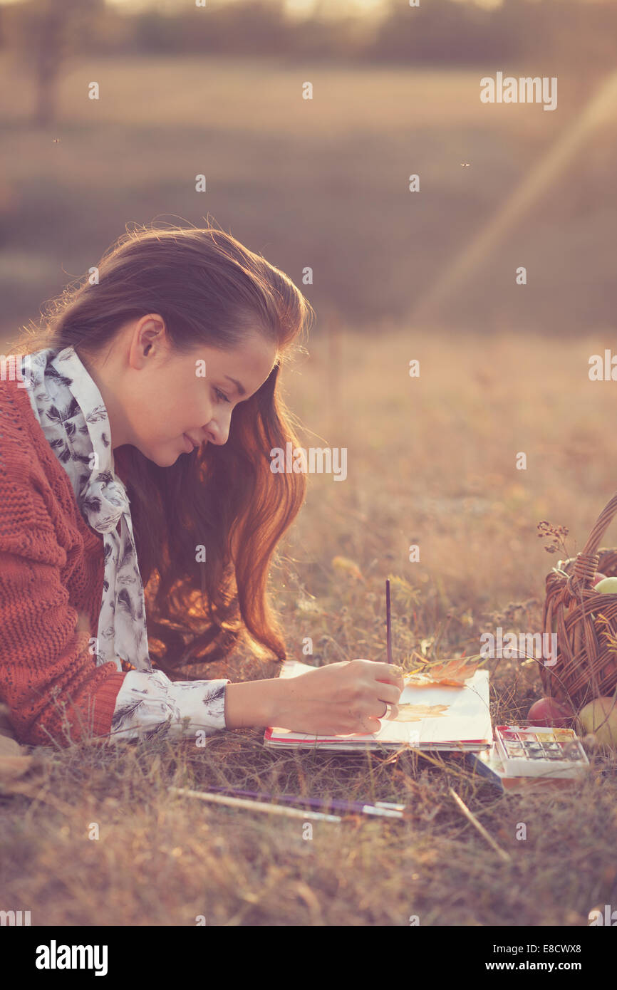 Lying Hipster styled woman drawing - Stock Image