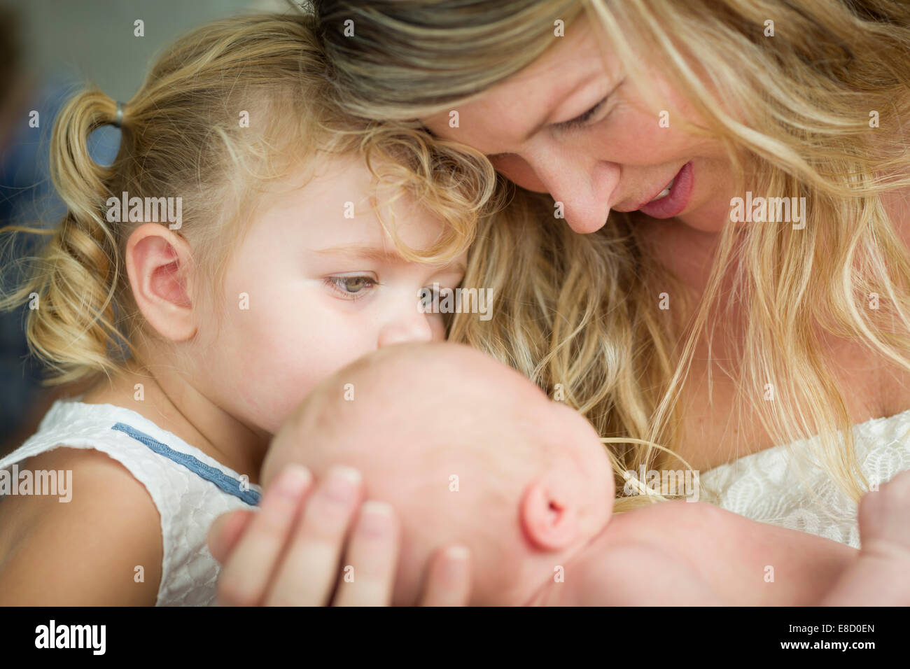 Beautiful Young Mother Holds Newborn Baby Girl as Young Sister Looks On. - Stock Image