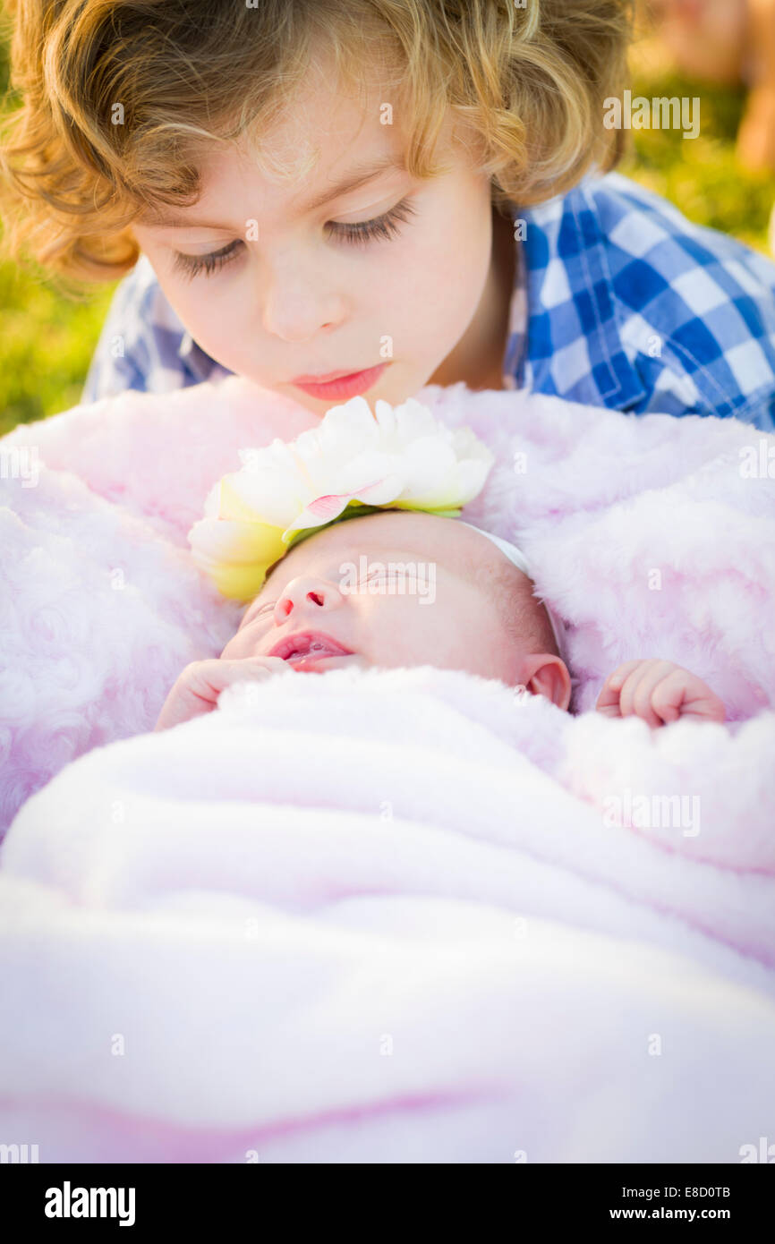 Cute Young Boy Gazing at His Newborn Baby Girl Sister. - Stock Image