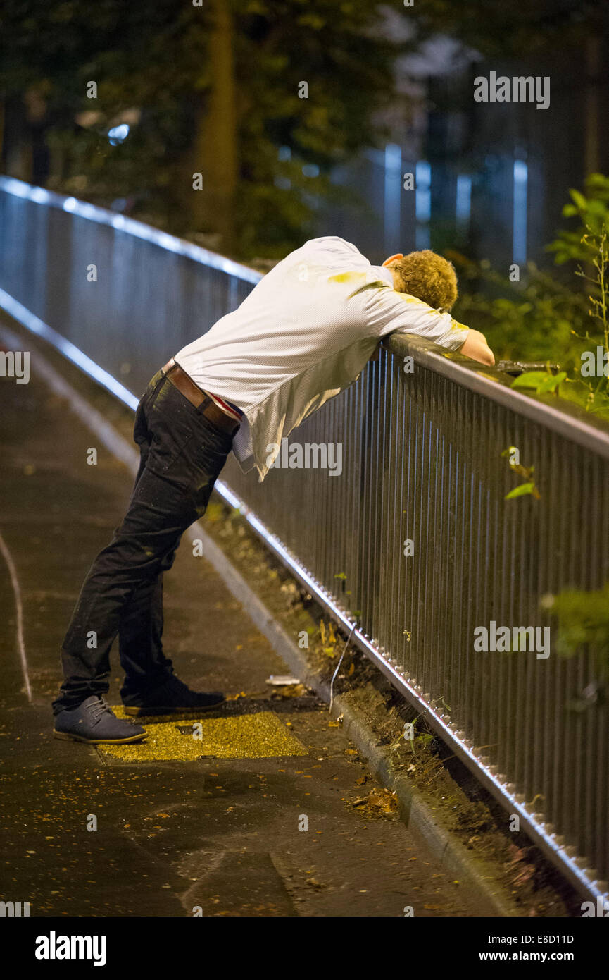 A drunk youth leans over railings after a night of heavy binge drinking in Cardiff, Wales. - Stock Image
