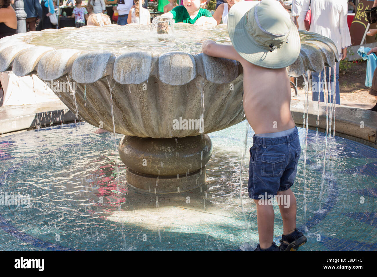 Child playing with water in fountain on a hot day at Sebastopol farmer's market, Sonoma County, California - Stock Image