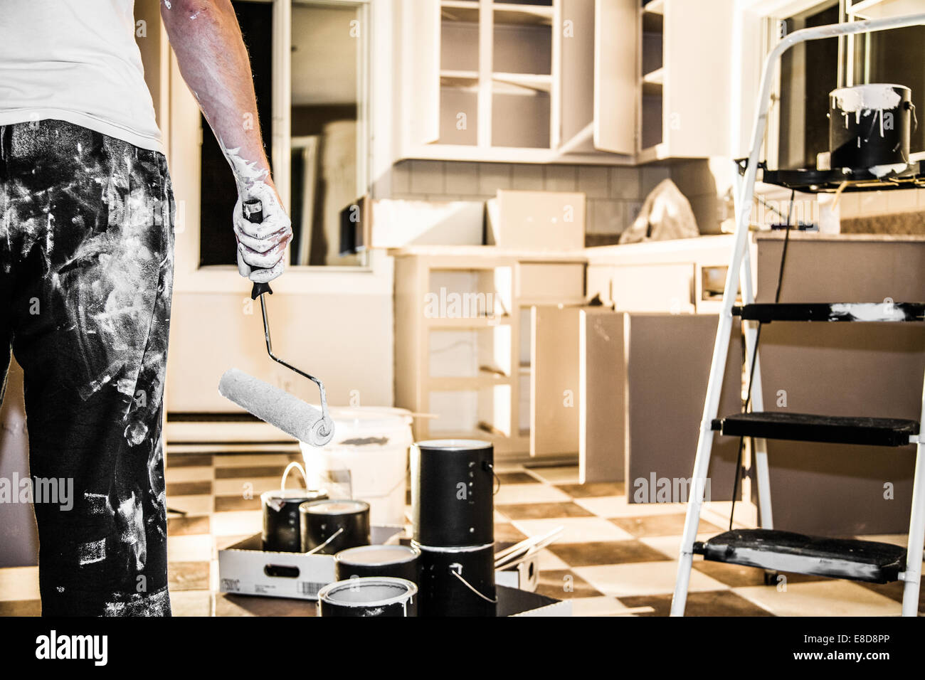 Mess of All kind of Painting Equipment in the Kitchen and Discouraged Man - Stock Image