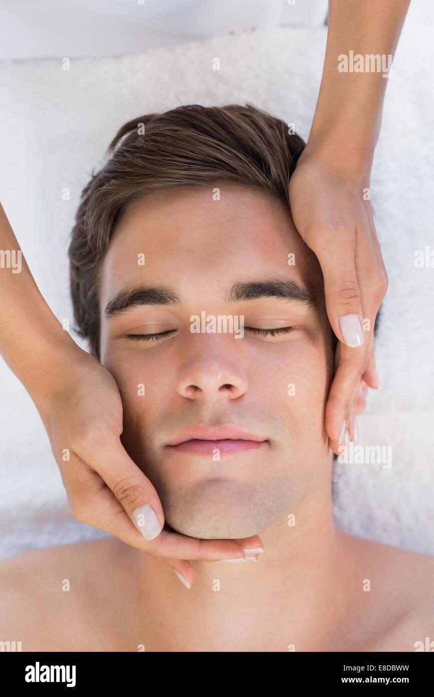 Man receiving facial massage at spa center - Stock Image