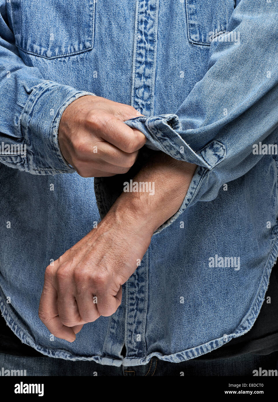 Man in denim shirt rolling up his sleeves - Stock Image