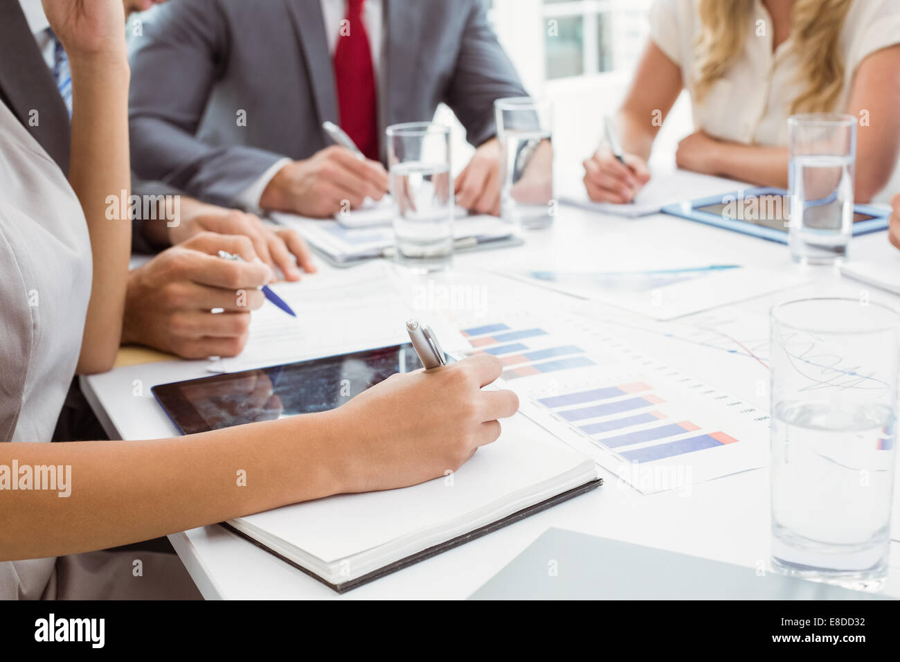 Mid section of executives writing notes in board room meeting - Stock Image