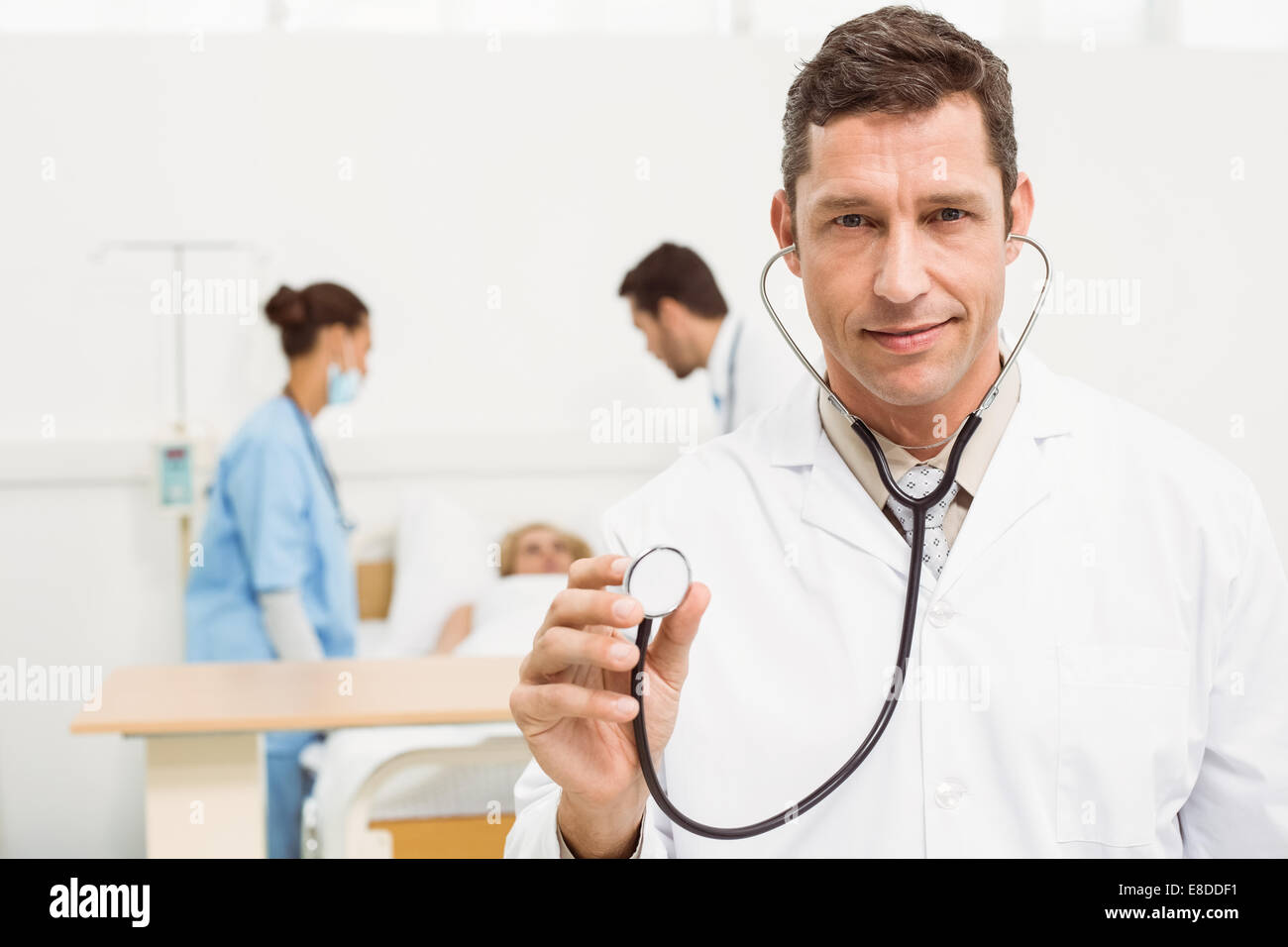 Doctor using stethoscope with colleagues and patient behind - Stock Image