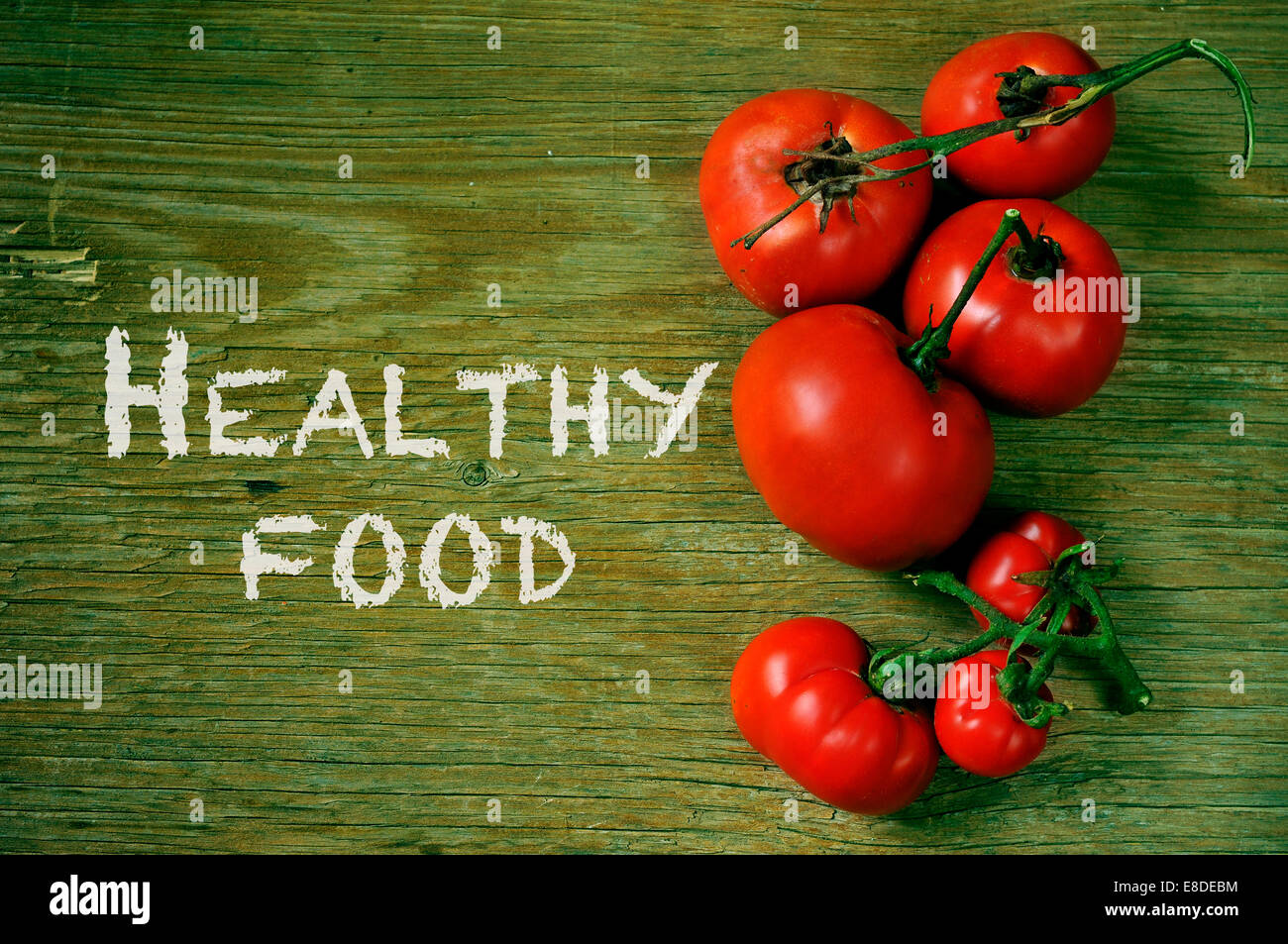 the text healthy food and a bunch of ripe tomatoes on a rustic wooden table - Stock Image