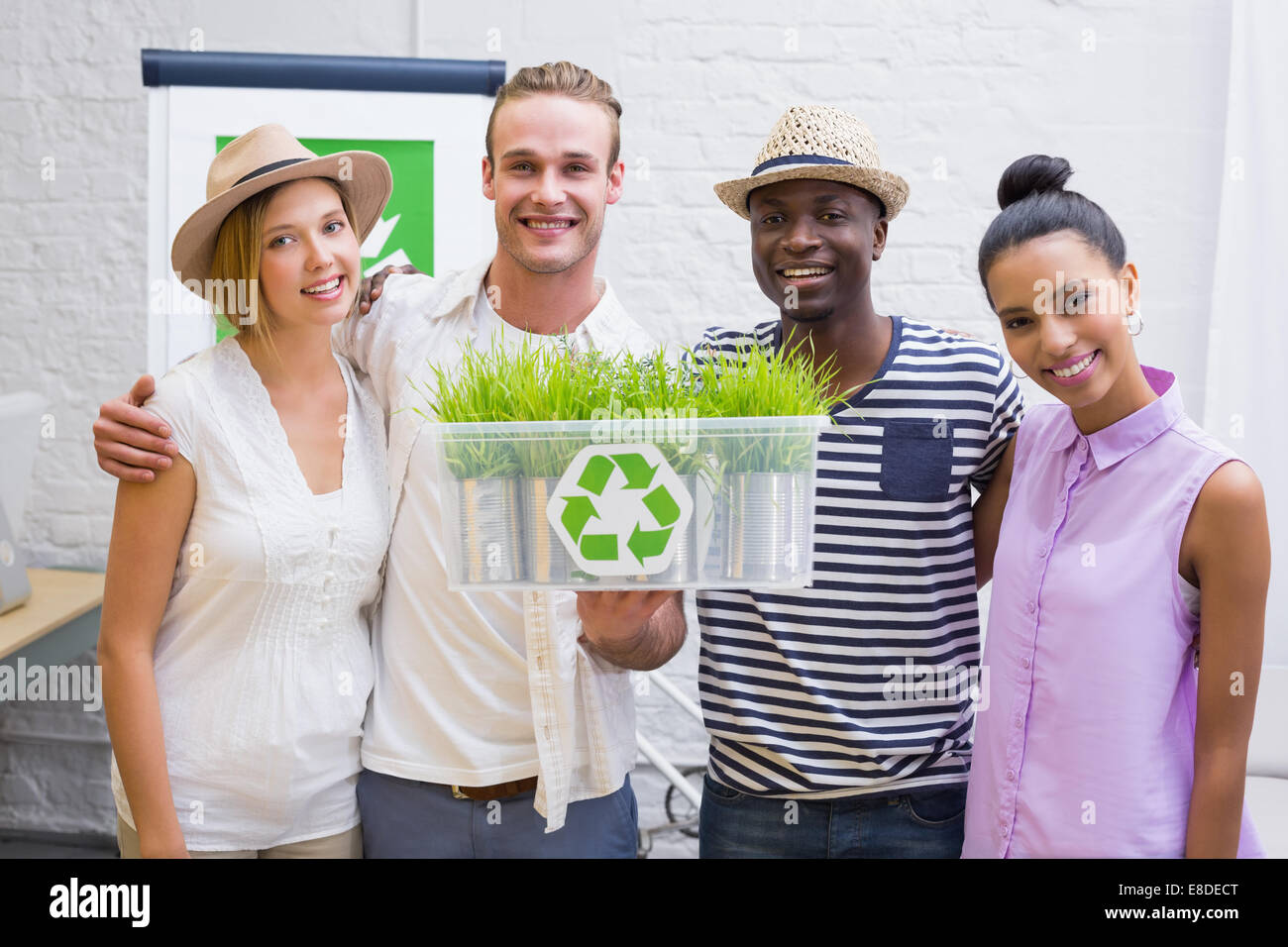 Creative business team holding plant with recycling symbol - Stock Image