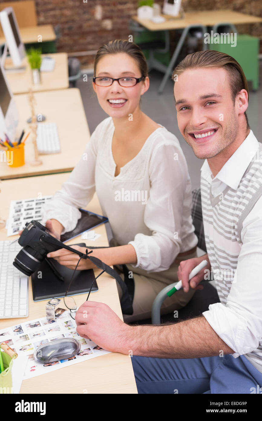 Casual photo editors with camera in office - Stock Image