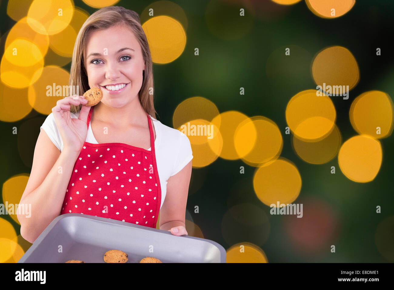 Composite image of pretty homemaker showing hot cookies - Stock Image