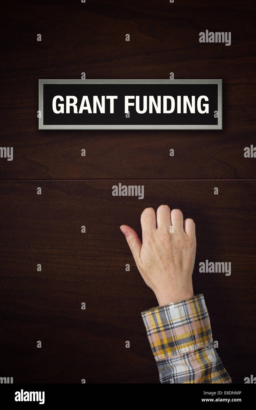 Female hand is knocking on Grant Funding door, conceptual image. - Stock Image