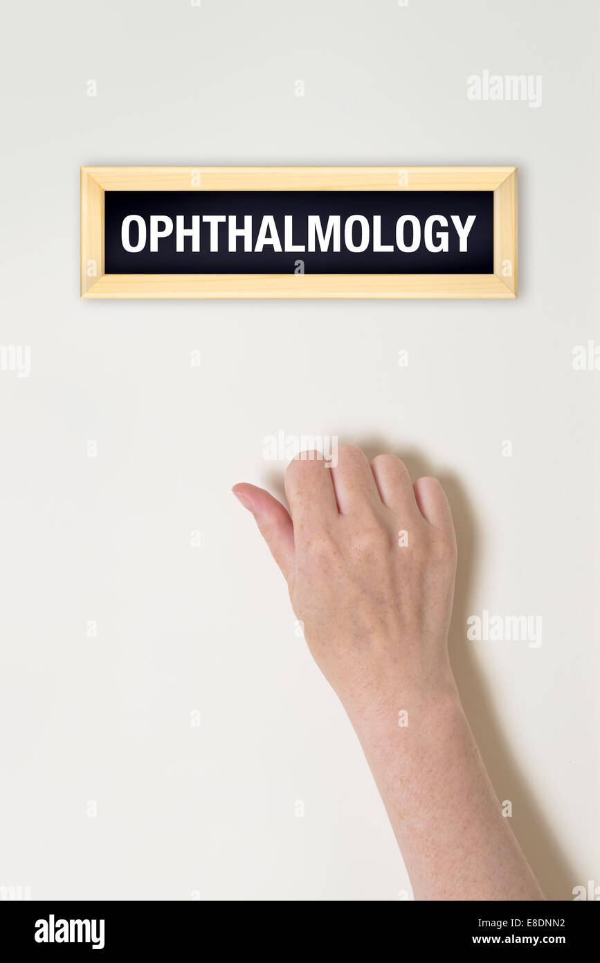 Female hand is knocking on Ophthalmology door for a medical exam - Stock Image