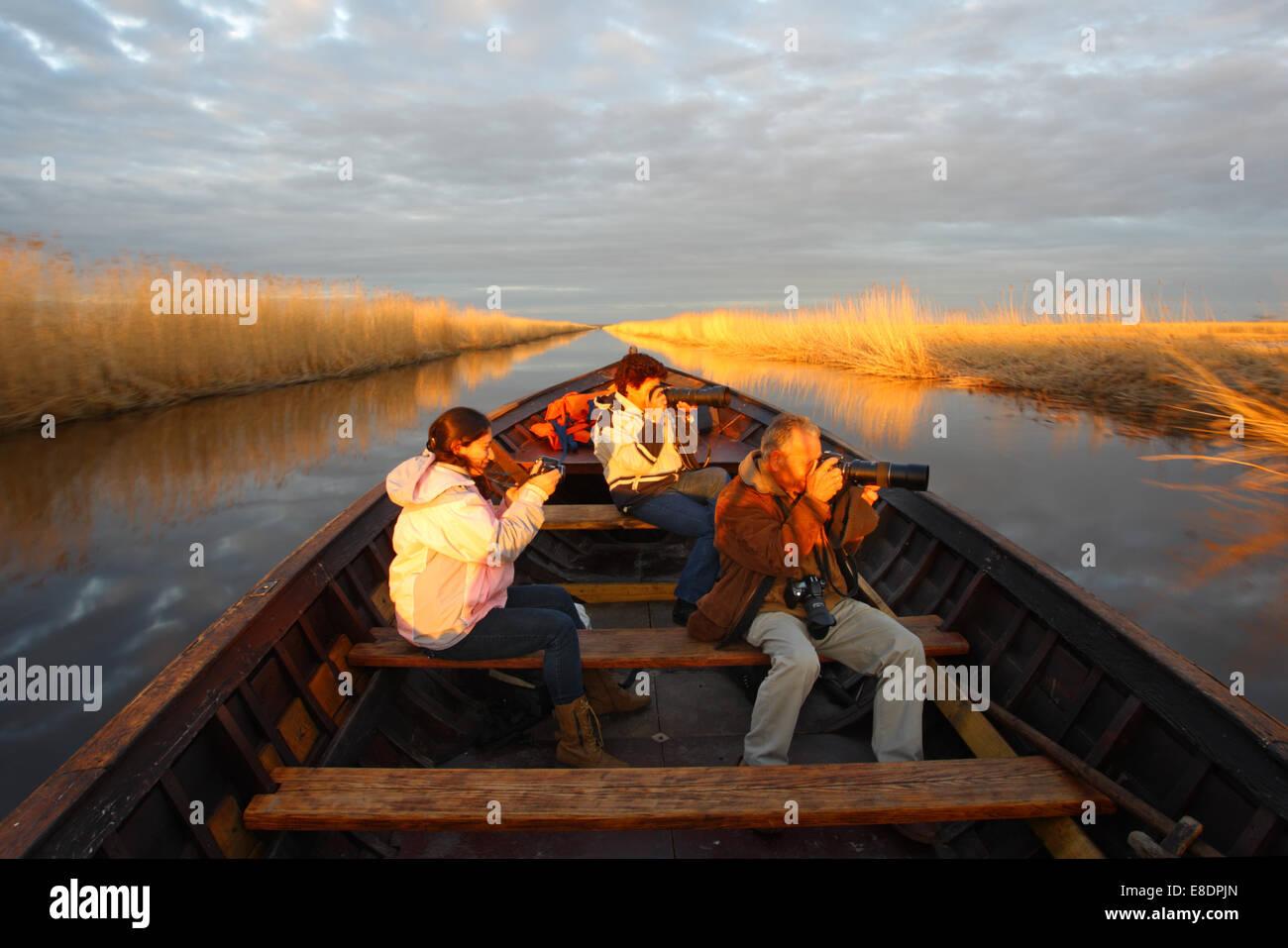 Family of photographers taking a boat trip on Kasari river, Matsalu National Park, Estonia - Stock Image