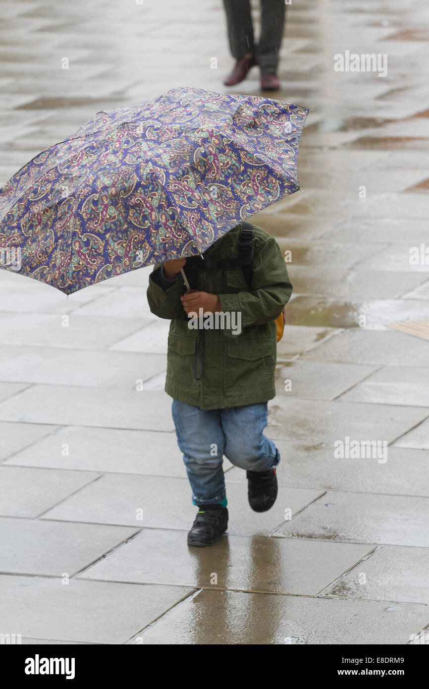 London, UK. 6th October, 2014. UK weather. Pedestrians shelter with umbrellas as they struggle with the  wet and Stock Photo