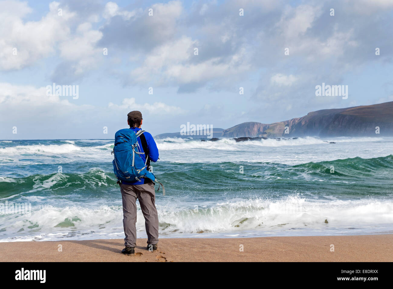 Walker and Stormy Sea, Sandwood Bay North West Scotland UK - Stock Image