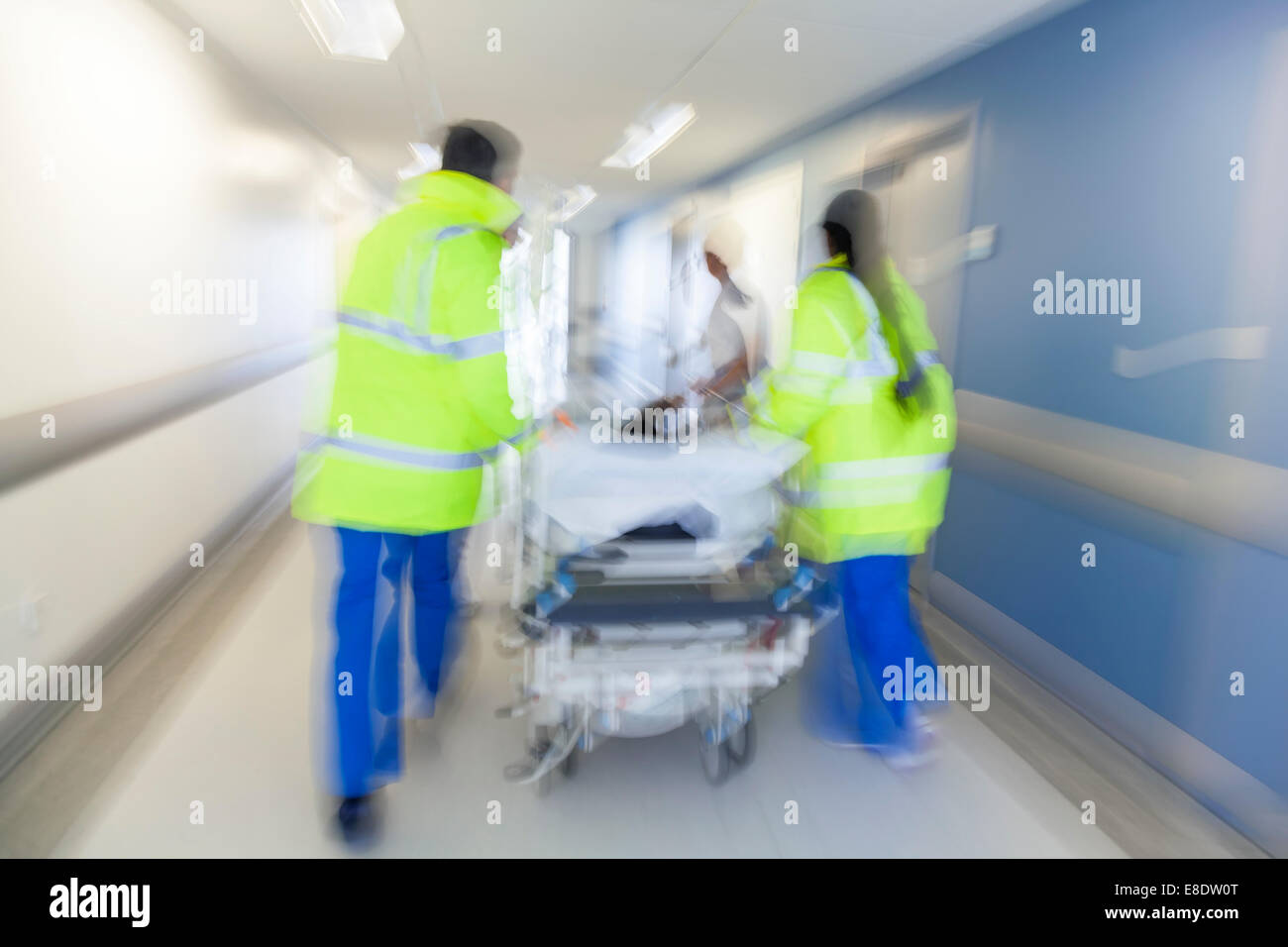 Motion blurred photo of patient on stretcher gurney pushed at speed through hospital corridor by doctors paramedics - Stock Image