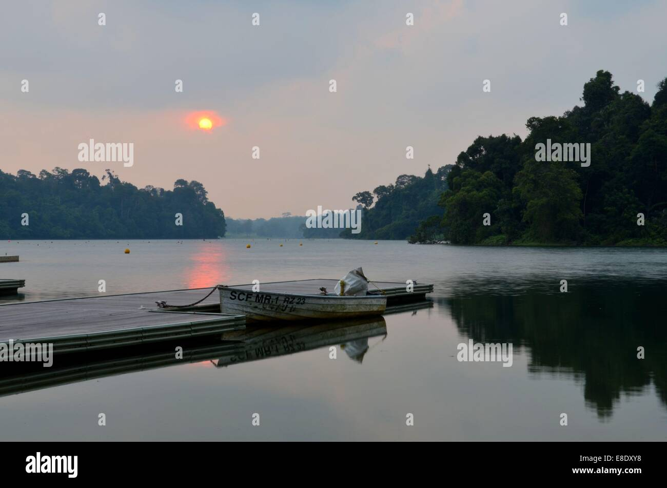 Sunset at Singapore MacRitchie Reservoir lake pier with parked boat in foreground - Stock Image