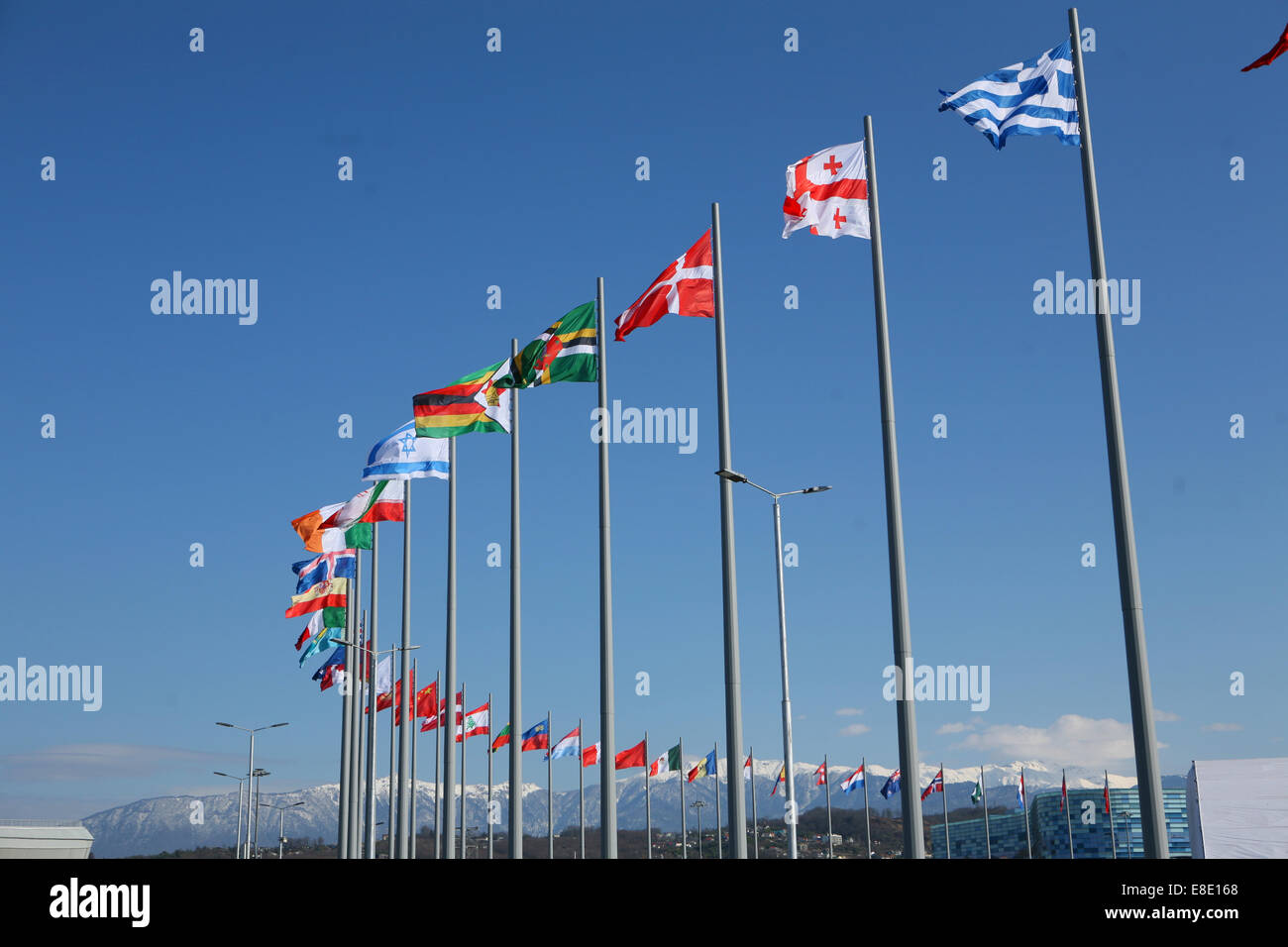 Curve of international flags mountains in the background Sochi - Stock Image