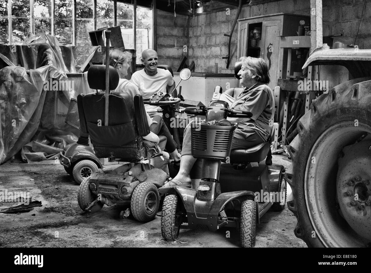 three people sitting on mobility scooters chatting in an old tractor shed - Stock Image