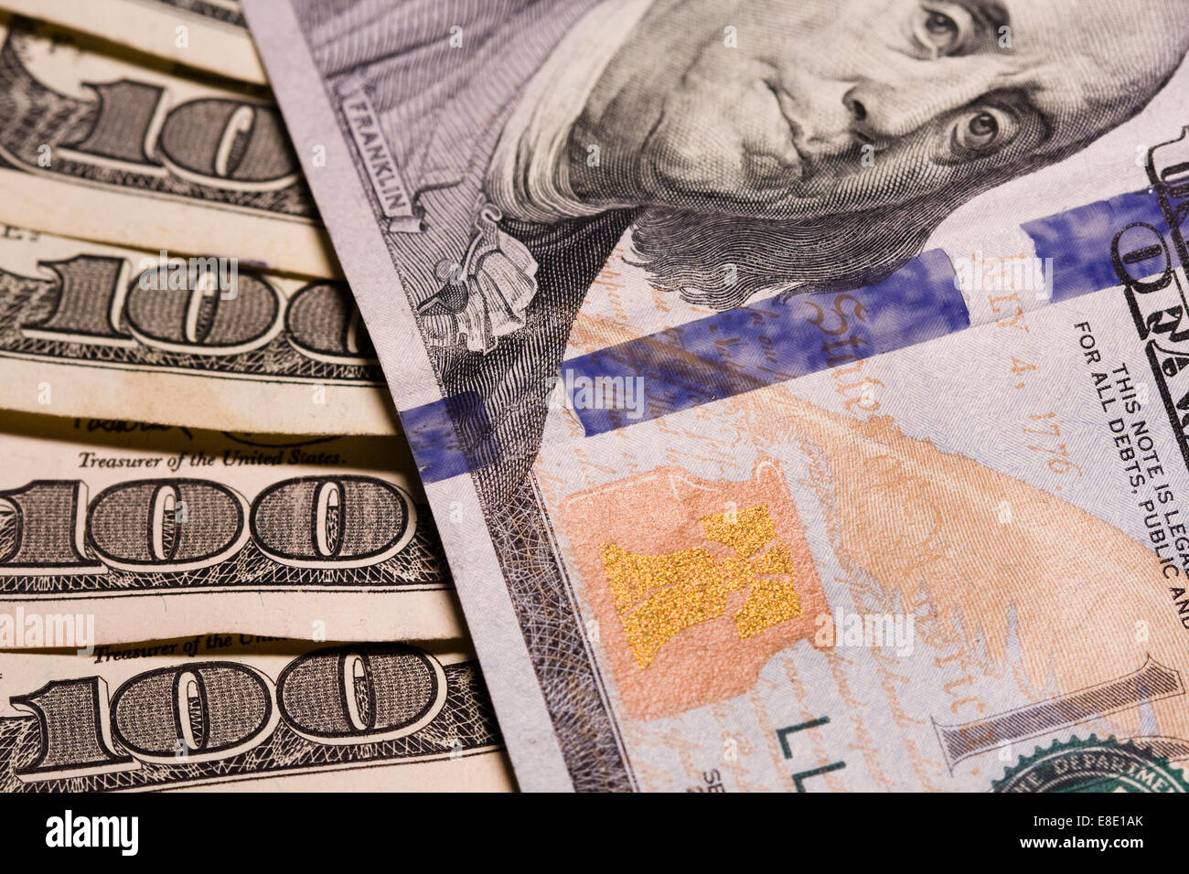 Many Hundred Dollar bills showing micro printing, color reflective gold feather, gold bell and inkwell and 3D security - Stock Image