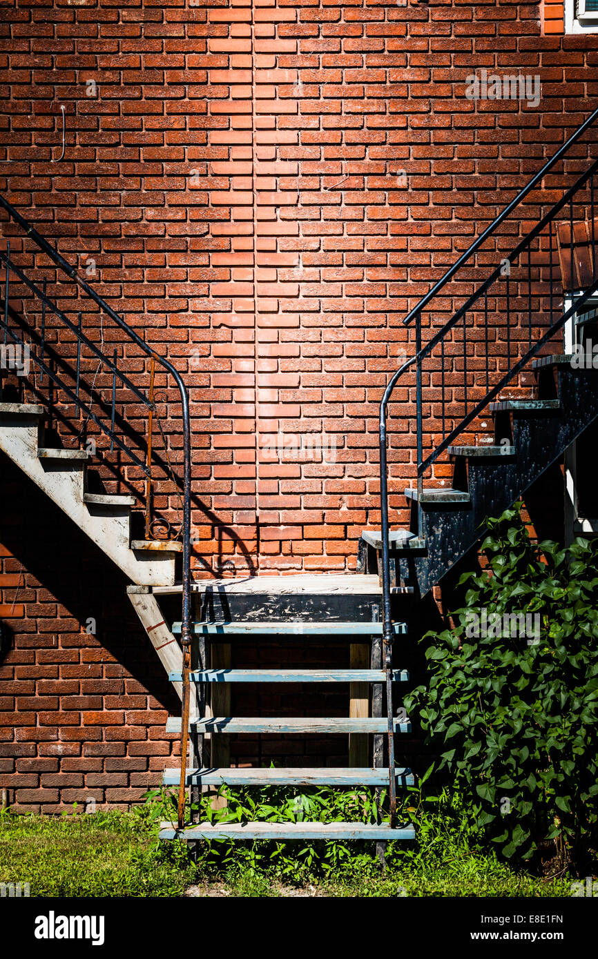 Symmetrical Staircases merging together and brick wall - Stock Image