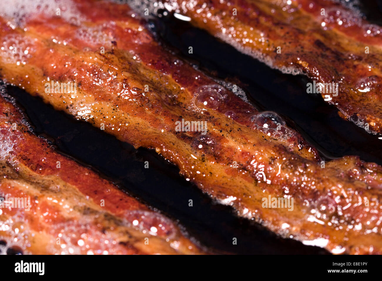 Bacon grease rendering out of strips of streaky bacon in a frying pan - Stock Image