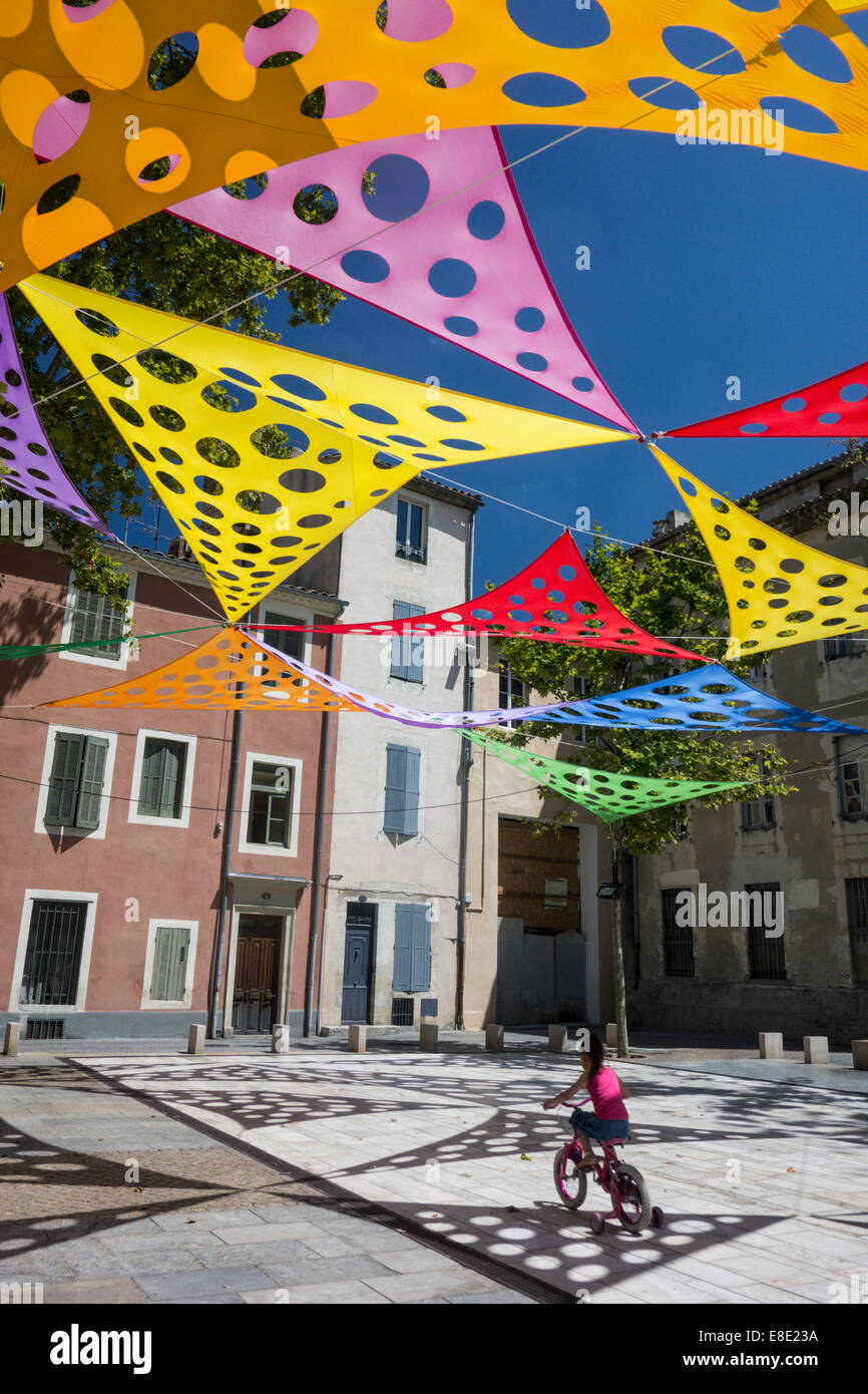 girl rides bicycle under colorful art panels in Place du Chapitre square in Old Nimes; Nimes; Gard; France - Stock Image