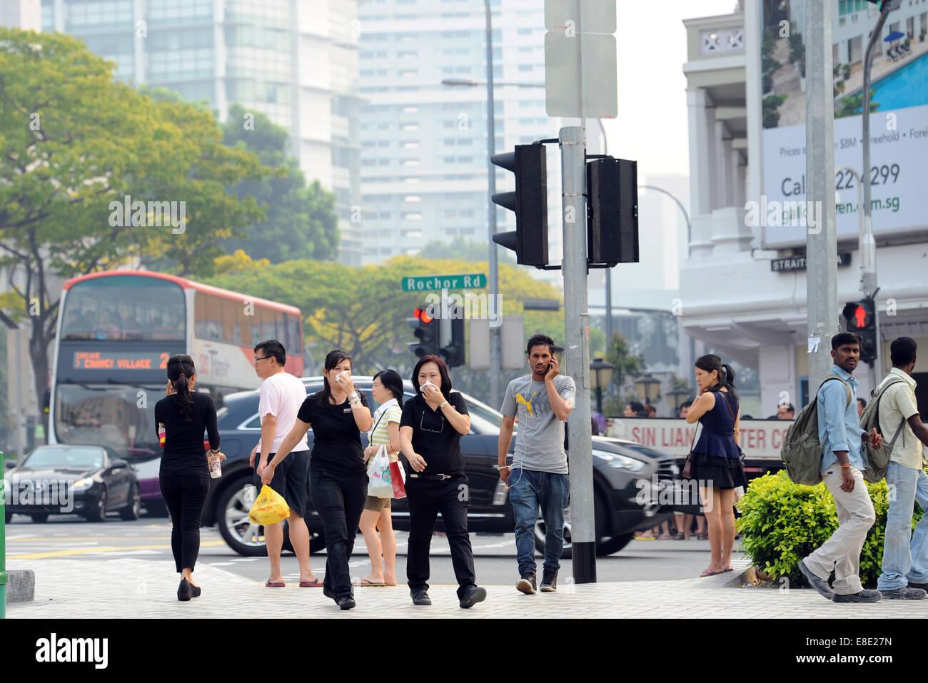 (141006) -- SINGAPORE, Oct. 6, 2014 (Xinhua) -- Pedestrians cover their mouths in Singapore, Oct. 6, 2014. Singapore's - Stock Image