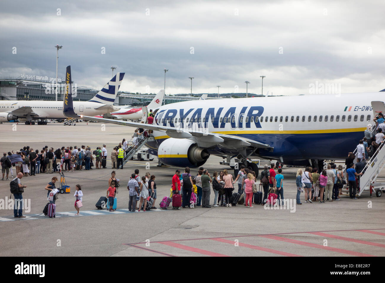 passengers line up to board Ryanair jet airliner on tarmac of airport in Marseilles in Provence South of France - Stock Image