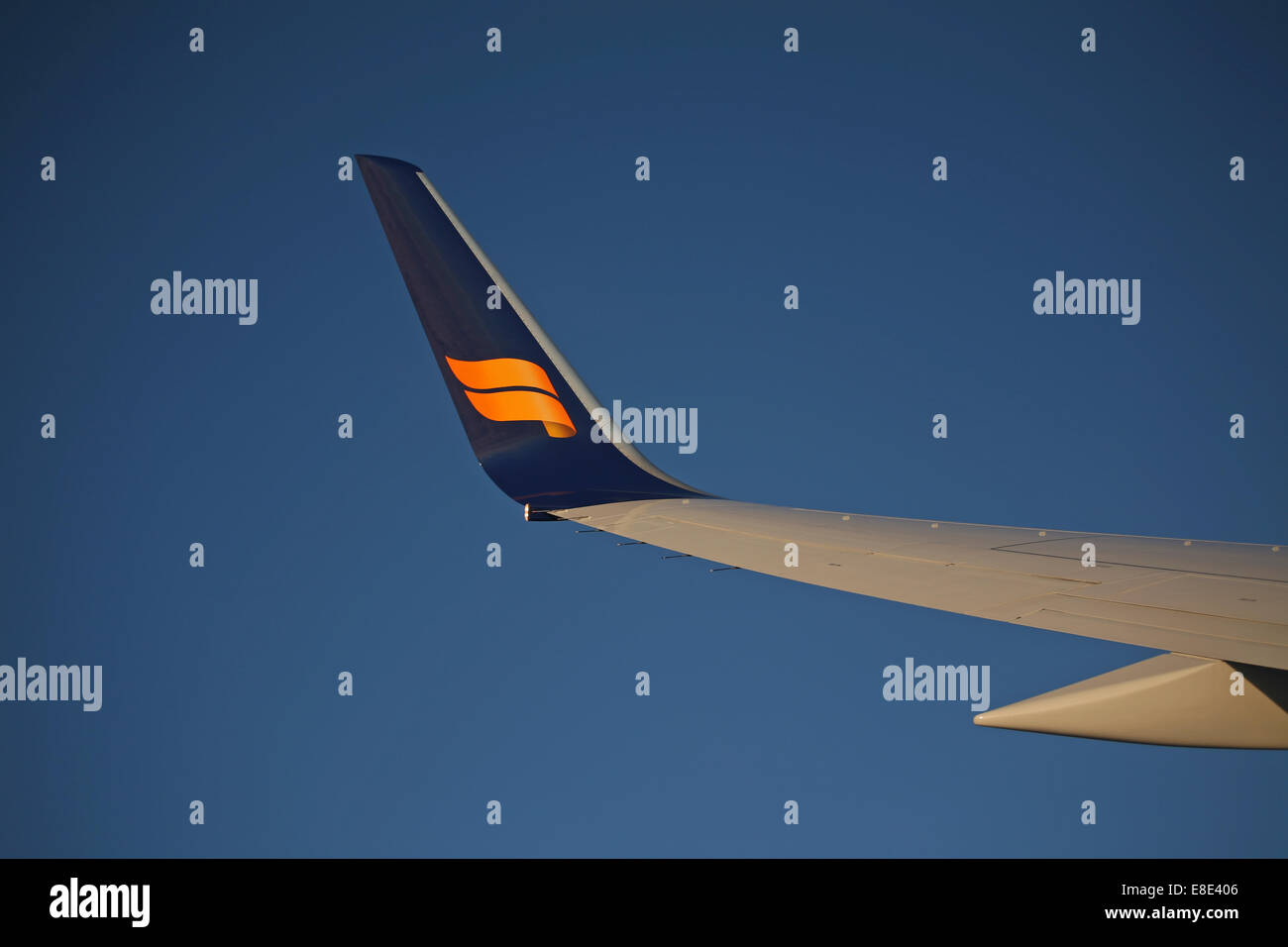 Icelandair logo on a winglet in blue sky flying seen from the cabin - Stock Image