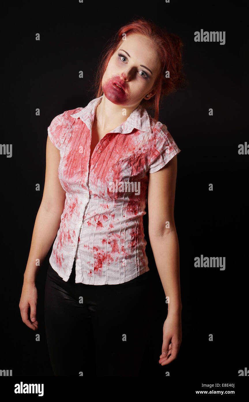 female zombie with bloody mouth and blouse on black background - Stock Image