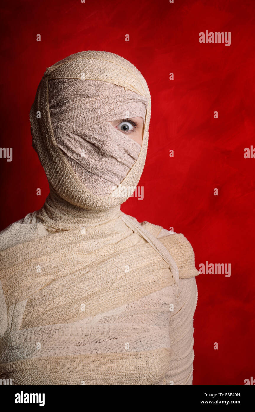 wide-eyed female mummy covered in bandages - Stock Image