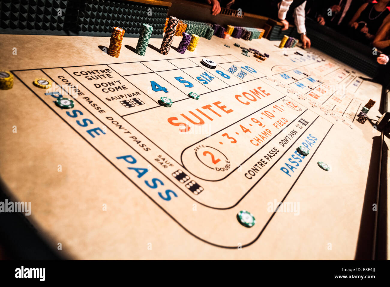 Craps Table, Chips Piles and People Gambling all Around - Stock Image