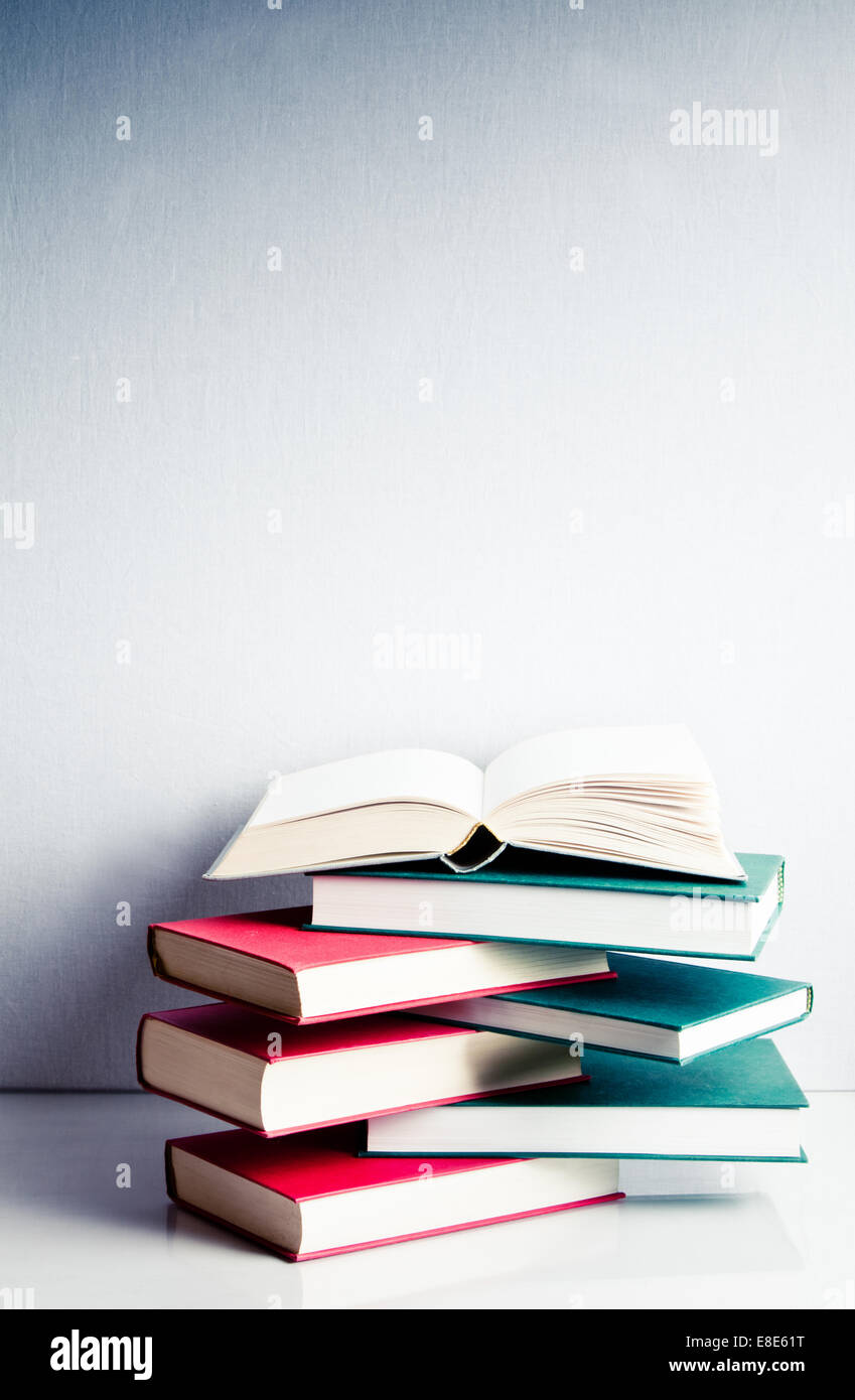 Blank open book on a green and red stack of books in balance - Stock Image