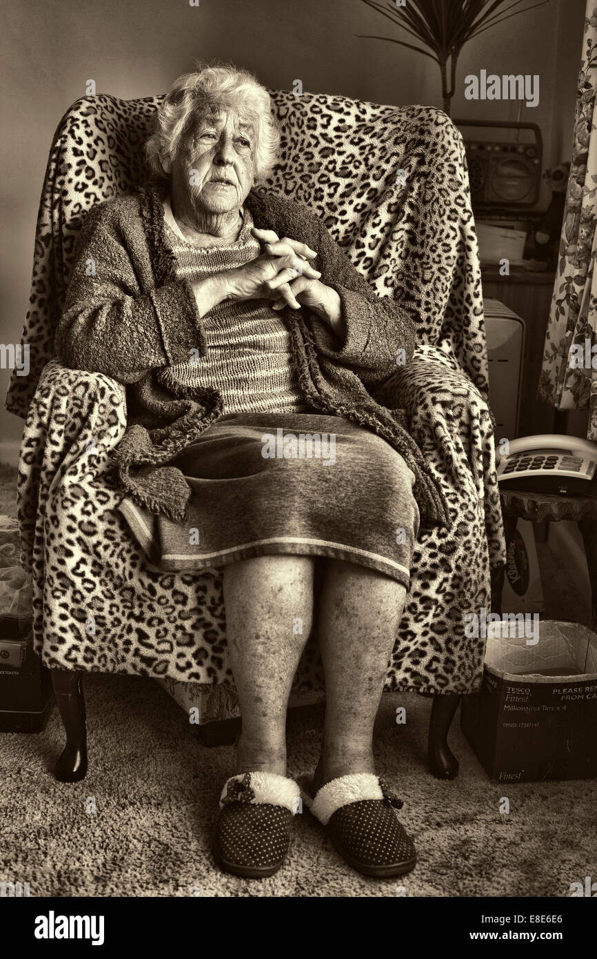 An elderly lady sitting in her chair reminiscing. - Stock Image