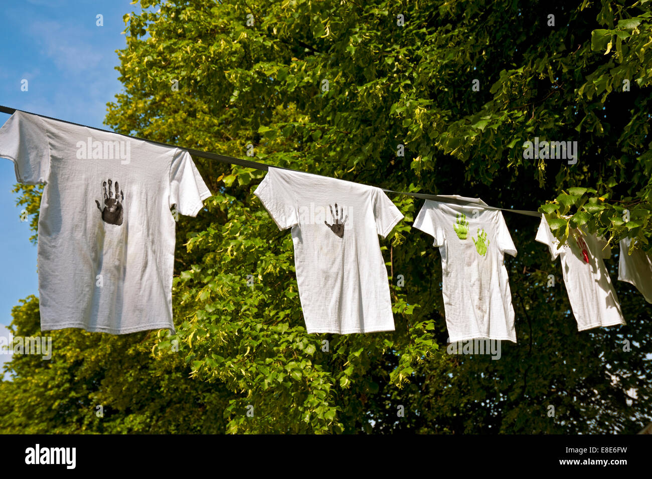 Tee shirts decorated with hand prints on a line North Yorkshire England UK United Kingdom GB Great Britain - Stock Image