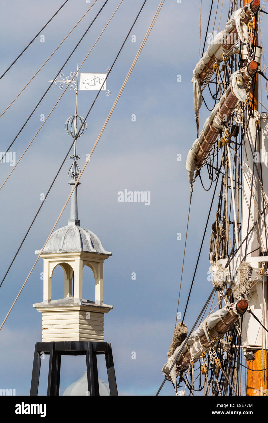 Mast and rigging of a tall sailing ship and bell tower and wind vain by the Lloyds Building on Bristol's floating - Stock Image