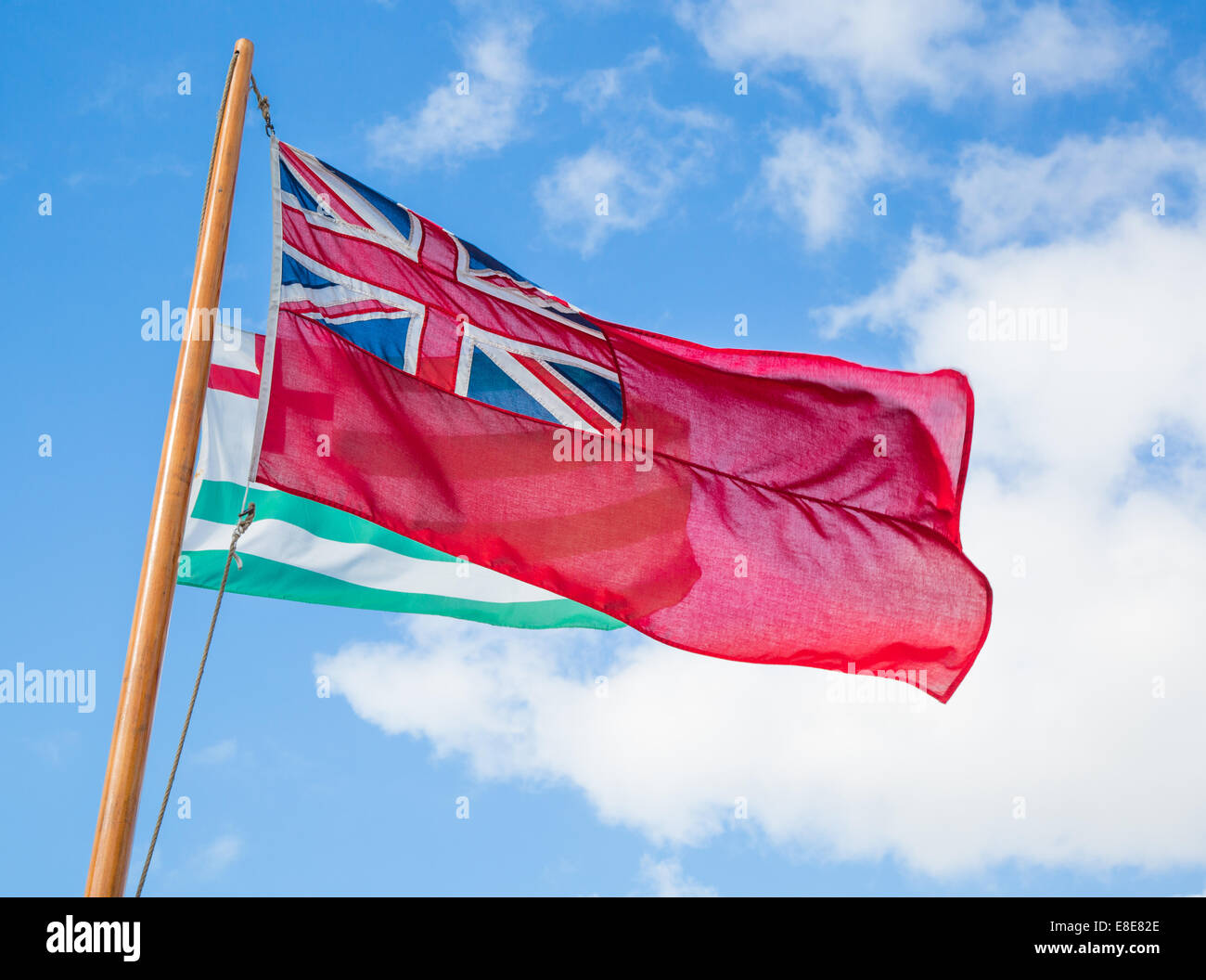 The Red Ensign or ' Red Duster ' flag hoisted on the mast of a sailing boat - Stock Image